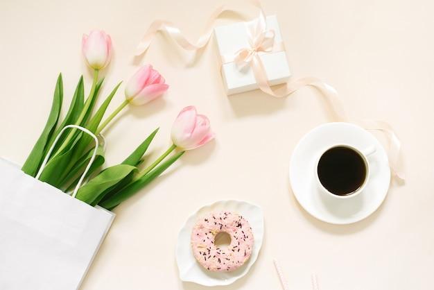 Утренняя чашка кофе, пончик, подарочная или настоящая коробка и весенние тюльпаны на бежевом фоне. красивый завтрак на женский день, день матери, день святого валентина. плоская планировка.