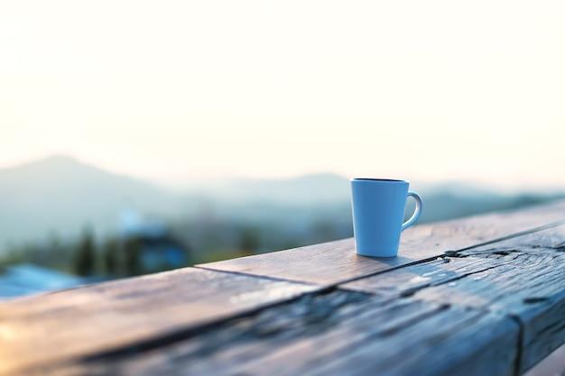 日の出の山の背景とコーヒーやお茶の朝のカップ