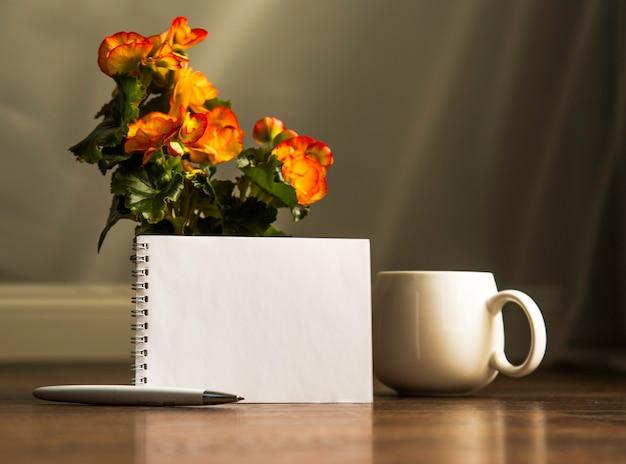 나무 테이블에 종이 메모장과 함께 아침 커피 한잔. 복사 공간입니다. 플래너 모형.
