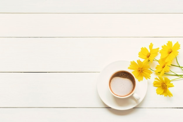 Утренняя чашка свежего кофе капучино с весенними желтыми цветами на белом деревянном столе.
