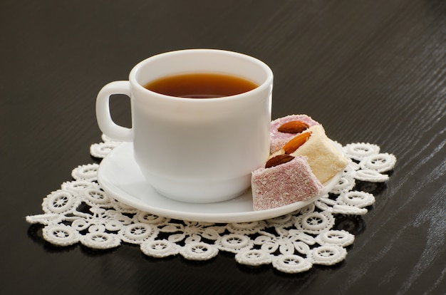 Morning cup of tea, turkish delight in a saucer on the black desk