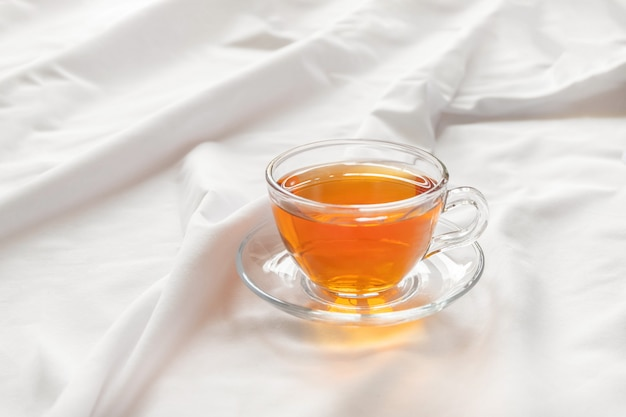 Morning cup of tea on white bed sheet with copy space. good morning concept.