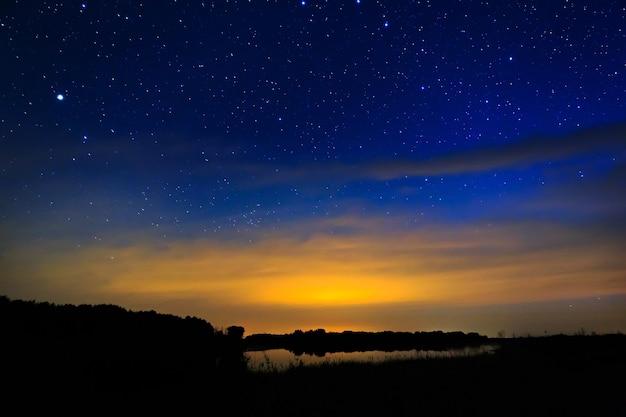 Утренний рассвет на звездном фоне неба отражается в воде озера.