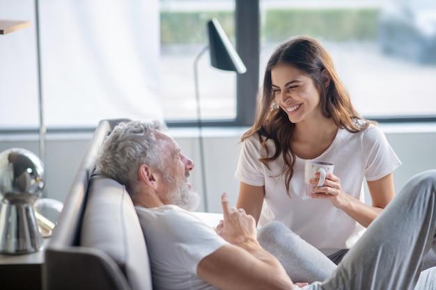 Утро, выходной. бородатый ужин лежит, разговаривает, жестикулирует и сияет, длинноволосая женщина с кофе сидит рядом и слушает