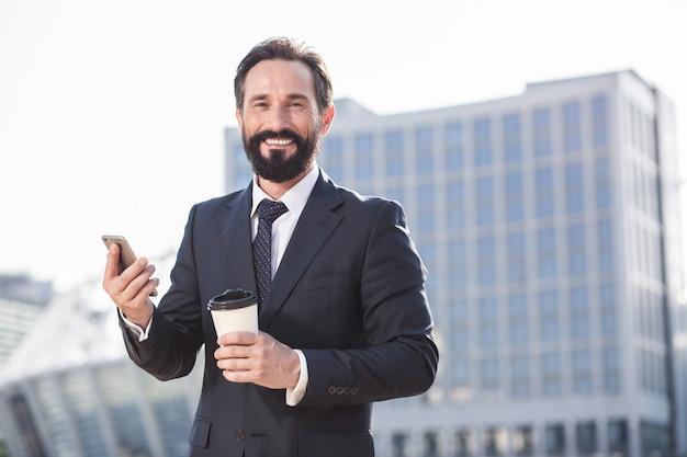 朝の飲み物。街を歩きながらコーヒーを飲む陽気な笑顔のビジネスマン