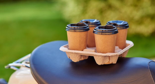 Утренний напиток из четырех бумажных кофейных чашек, стоящих на скутере селективный фокус