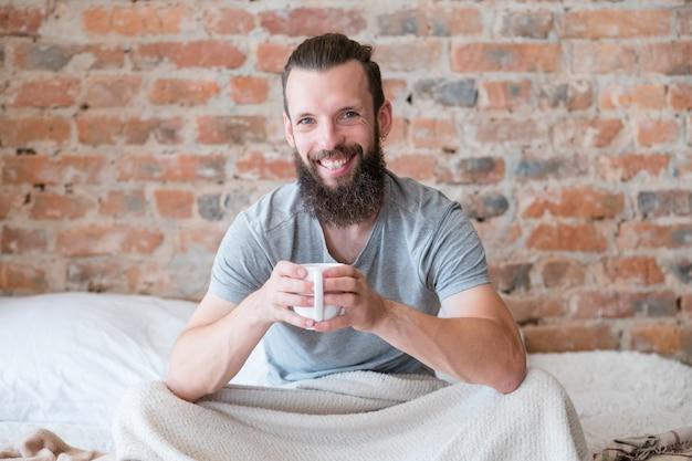 Утренний напиток тепла и энергии. новый день. восстань и сияй. улыбающийся хипстер в постели с чашкой напитка.