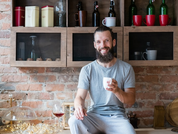 Утренний напиток тепла и энергии. восстань и сияй. счастье. улыбающийся бородатый битник, сидя на кухонном столе с чашкой.