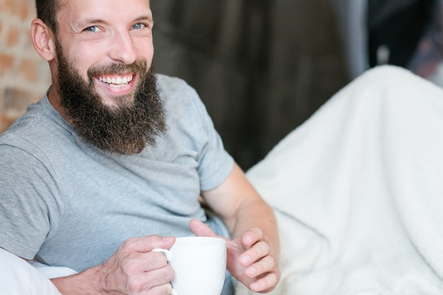 Morning drink warmth and energy. new day. rise and shine. smiling hipster in bed with cup of beverage.