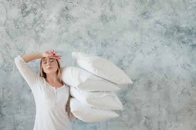 朝の義務。寝具の手配。枕の山を保持している疲れた若い女性。