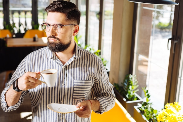 Morning espresso. serious young man holding a cup with coffee while wanting to drink it