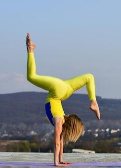아침 운동. 우크라이나 국가대표 체조 선수. 곡예와 체조. 야외 스트레칭 소녀 요가입니다. 필라테스 스튜디오 온라인. 매력적인 젊은 스포티 한 여성이 야외 체육관에서 운동하고 있습니다.