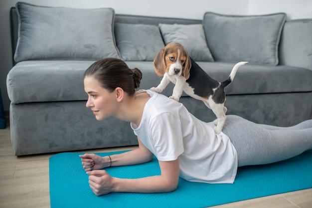 Утренняя гимнастика. девушка в белой футболке тренируется вместе со своим щенком