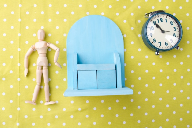 Morning exercises concept toy man miniature with cupboard and alarm clock on yellow background flat ...