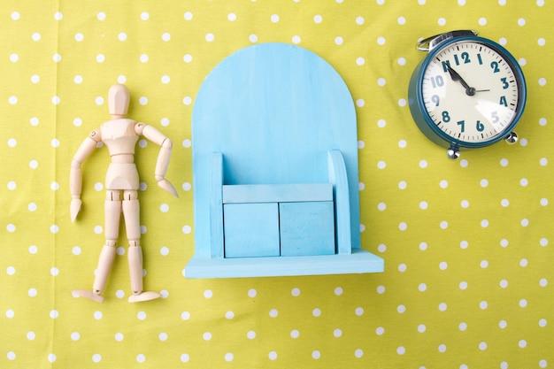 朝のエクササイズのコンセプトおもちゃの男のミニチュア、食器棚と黄色の背景の目覚まし時計フラット...