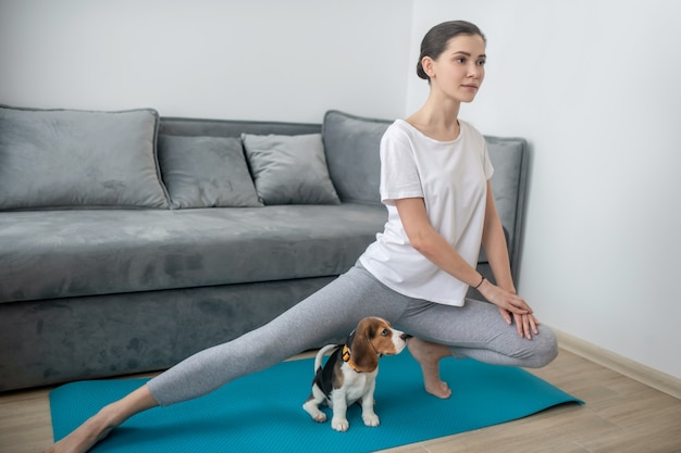 Morning exercises. a girl in a white tshirt exercising together with her puppy