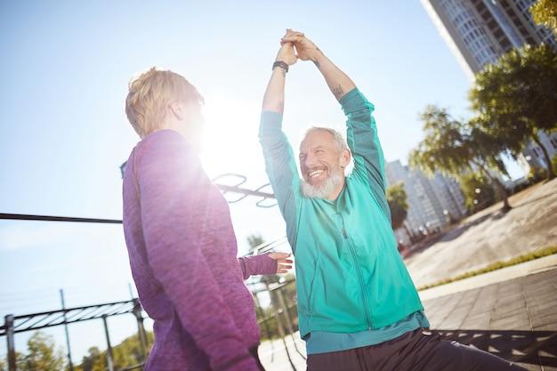 아침 운동은 스포츠웨어를 입은 성숙한 가족 커플이 야외 체육관에서 함께 워밍업을 하고 있다