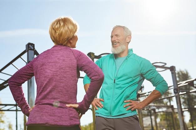 아침 운동은 야외 체육관에서 함께 체조를 하는 운동복을 입은 행복한 노인 가족 부부