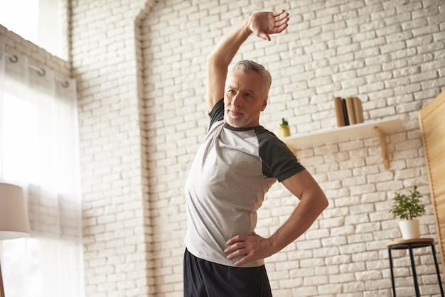 Morning exercises in room senior man stretching.