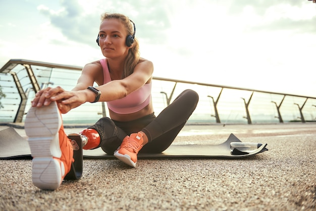 Утренняя зарядка молодая красивая женщина в наушниках с протезом ноги, слушая музыку и