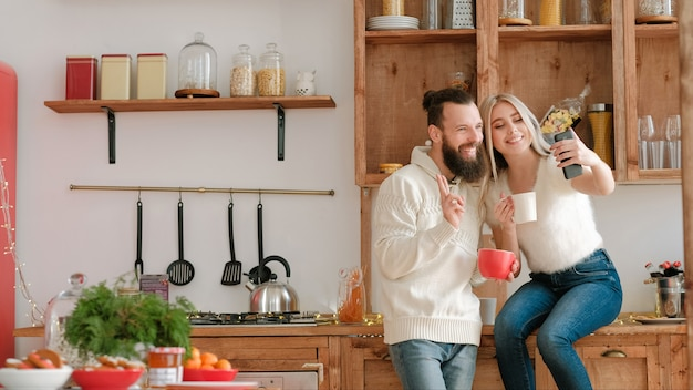 Morning family fun. couple drinking coffee in modern kitchen, using smartphone to take selfie.