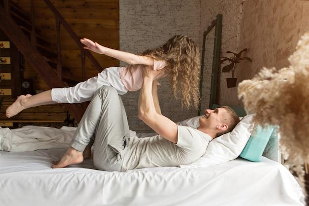 아침 가족 아이들은 침대에서 놀고 있는 아빠와 함께 꿈에서 깨어나 방금 사랑을 깼습니다.