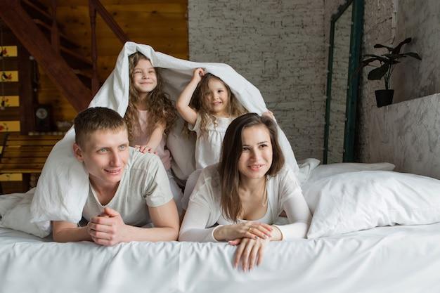 朝の家族夢から目覚めた両親と一緒にベッドで遊んでいる子供たち私はただ愛を目覚めさせた