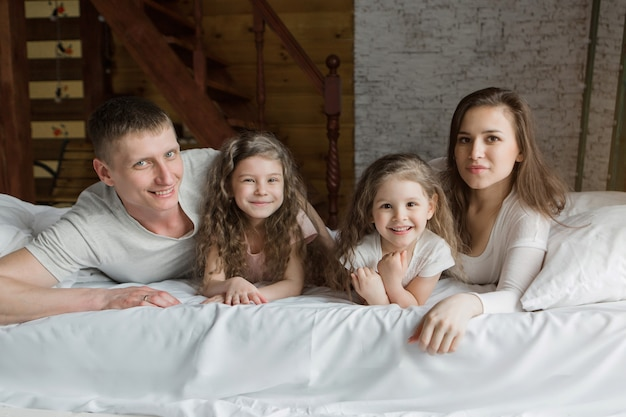 아침 가족 침대에서 노는 부모와 함께 꿈에서 깨어 난 아이들은 방금 사랑을 깼습니다.