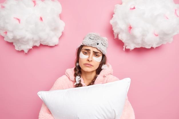 朝の倦怠感。動揺して眠い女性が目を覚ます間、家にいる間、枕を保持するのが難しい