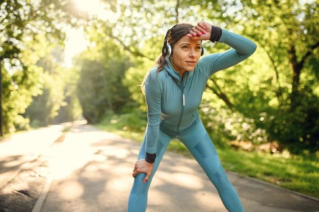 公園でのモーニングフィットトレーニング、歩道を走るヘッドフォンの女性