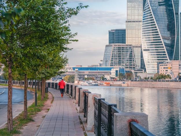 Утренний фитнес-забег на набережной в москве. рано утром мужчина в красной спортивной ветровке бежит по пустынной улице.