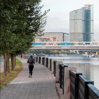 朝のフィットネスはモスクワの堤防で実行されます。早朝、女性が通りを駆け下ります。