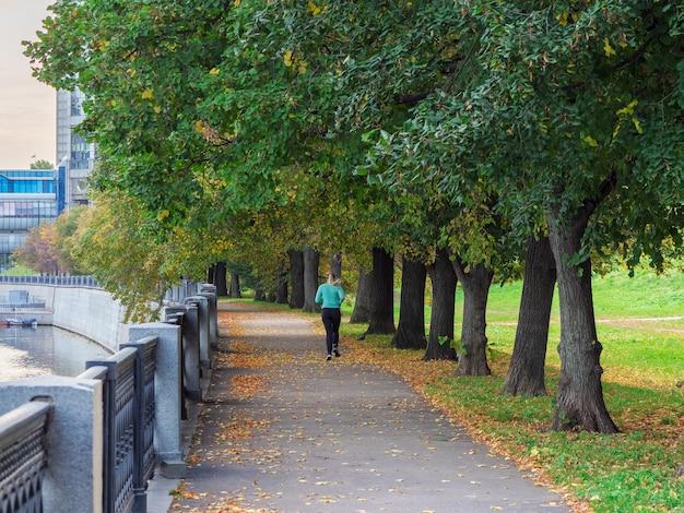 モスクワの堤防で走る朝のフィットネス。早朝、女性が通りを走ります。