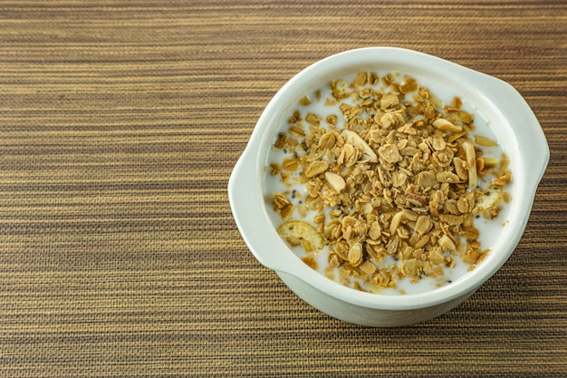 Morning food almond flakes  and milk in white bowl on wood table.