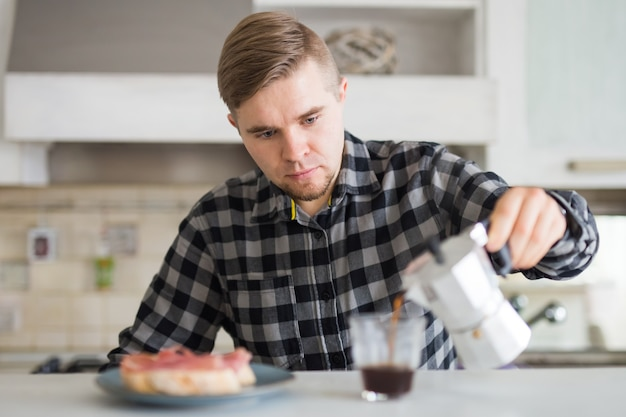 朝、食べ物、人々の概念-朝食にコーヒーを注ぐ男