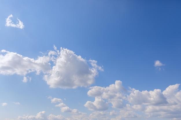 Утреннее свежее голубое небо с белыми облаками и солнечным светом слева (перспектива до горизонта)