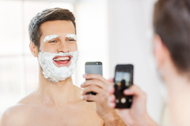Morning fun. rear view of playful young man with shaving cream on his face making selfie and smiling while standing in front of the mirror