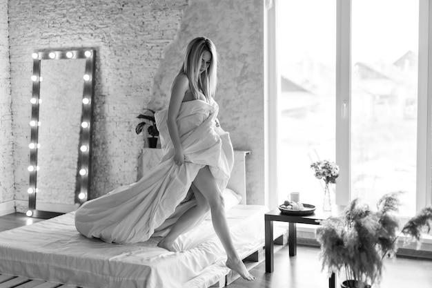 Утро девушки: блондинка в пледе сидит на кровати. просыпаясь ото сна. только что проснулся