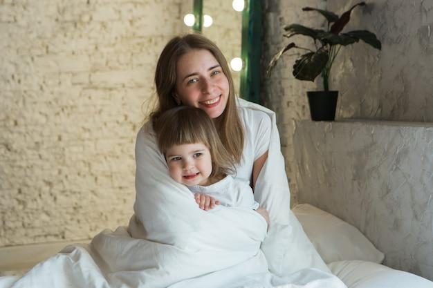 침대에서 놀고 있는 아이들과 함께 아침에 여자 엄마가 꿈에서 깨어나 방금 일어났습니다.