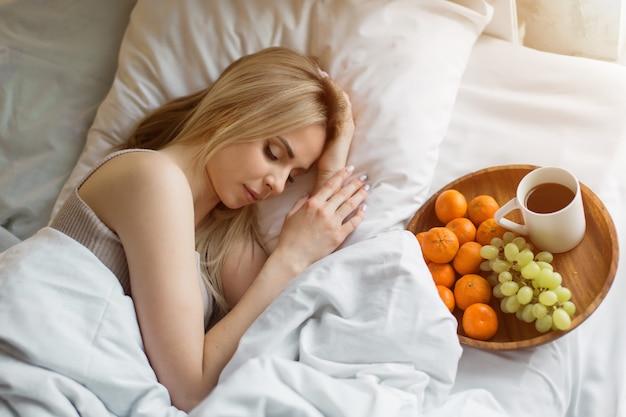 Утро девочки блондинка спит завтрак в постели я только что проснулся фрукты на тарелке