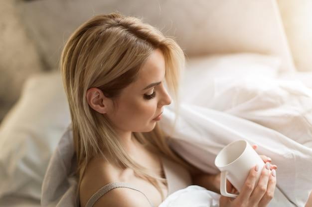 Утро девушки блондинка с чашкой чая кофе завтрак в постели я только что проснулась