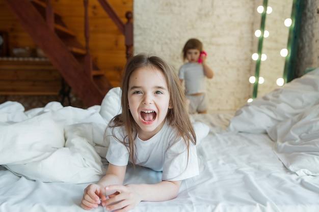 아침 소녀들은 침대에서 노는 아이들이 꿈에서 깨어나 방금 일어났습니다.
