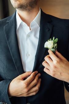 朝の新郎、ジャケットを着た新郎、新郎はボタンホールをまっすぐにする、結婚式の日