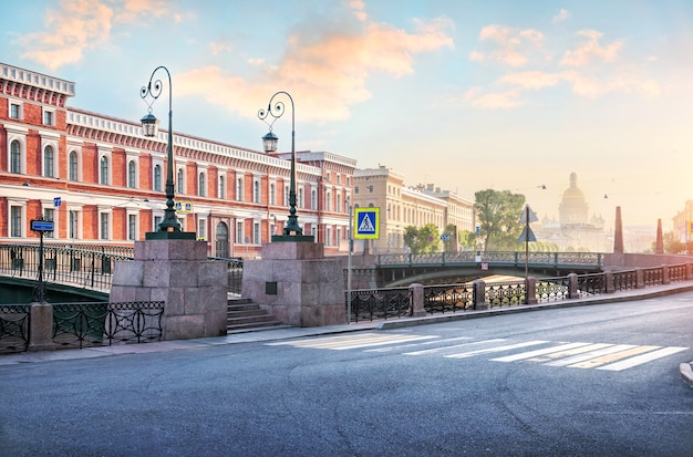 Утренняя дымка на мойке. мост поцелуев и исаакиевский собор в солнечном свете санкт-петербурга.