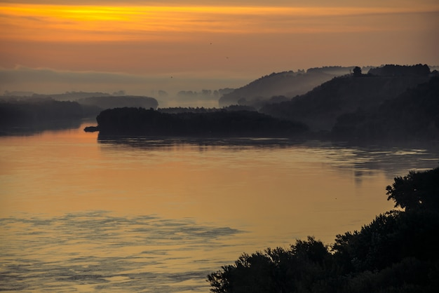 Morning haze above valley of river. gold glow from dawn in sky and reflex on water. birds flying in sky at sunrise. fog on riverbank with forest.