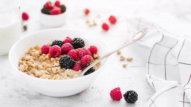 Утренний здоровый завтрак, белая миска, полная мюсли, мюсли, малина, ежевика на сером бетонном столе. здоровое питание, эко, концепция био продуктов питания. свежая вкусная еда на сером фоне. качественное фото