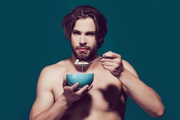 朝の健康的な食事とダイエット、オートミールを食べる裸の胸を持つ男。朝食用シリアル、男性またはスポーツ選手のための健康食品。