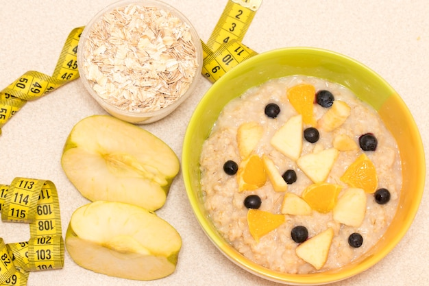 朝の健康的な栄養、オートミールのお粥、果物、巻尺付きのダイエットフレーム。トレーニング前の完璧な朝食