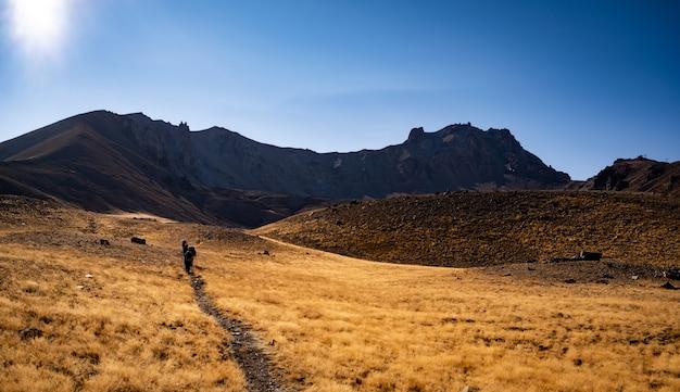 日の出の時間にトルコの火山での朝のハイキングバックパックを持った人々が山の頂上に登る