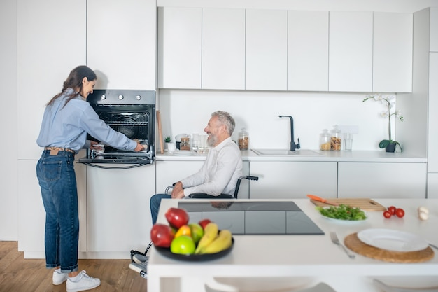 Morning at home. gray-haired handicapped man and his young wife in the kitchen getting the breakfast ready